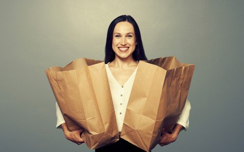 Woman holding shopping bags. Repeat customers are worth their weight in gold