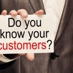 "Manage customer relationships. Man holding card that reads ""Do you know your customers?"""