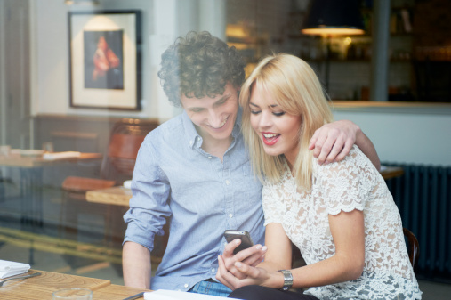 man and woman looking at phone: 5 ways to engage customers with CityGro